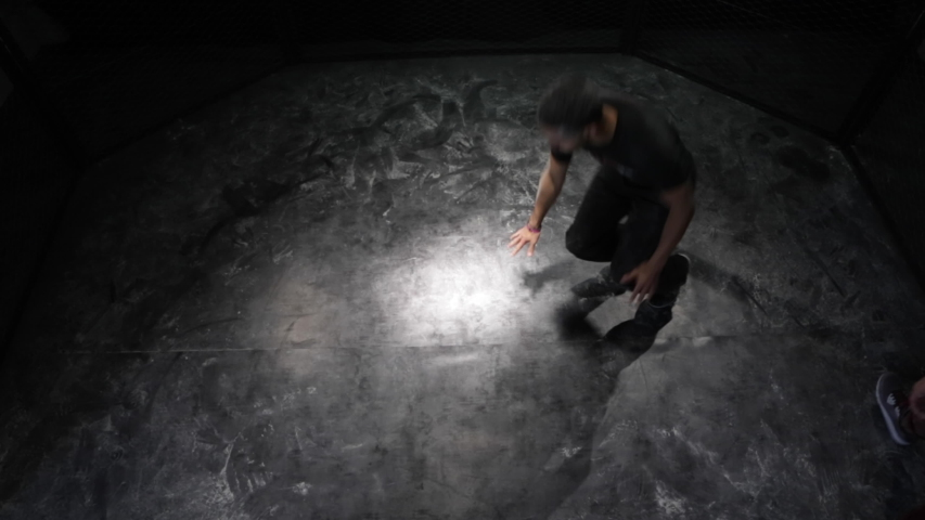 Paris, France - April 10, 2019: Break dancer in high angle dancing on a dirty floor with dust or white flour inside a metal cage. Body turning at full speed in slow motion 4K. Break dancing, Street. #1031914835