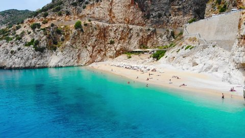 Aerial. Kaputas beach - it is one of the bays of Antalya, Turkey. Located near the city of Kas. The bay is washed by the Mediterranean Sea. We can sea tourists sunbathing and swimming. View above from
