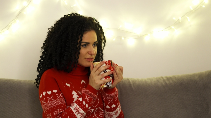 Spirit of christmas, with a young beautiful woman sipping on coffee and reminiscing memories (medium shot)   Shutterstock HD Video #1031976005