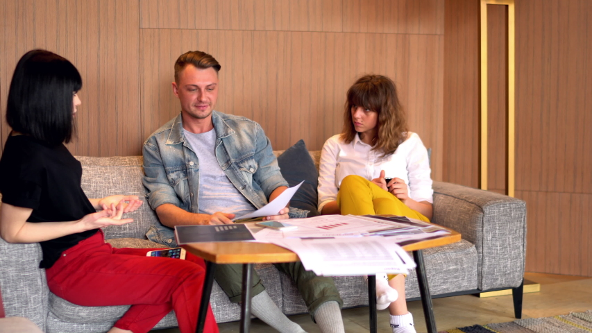 Professional colleagues in casual wear discussing productive strategy for development of startup having brainstorming meeting in office.Male and female designers collaborating on common task #1031980985