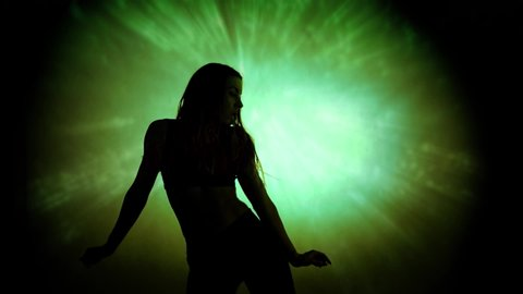 Silhouette of a young sexy woman dancing to 90 beats per minute bpm music  against a psychedelic green spotlight abstract background
