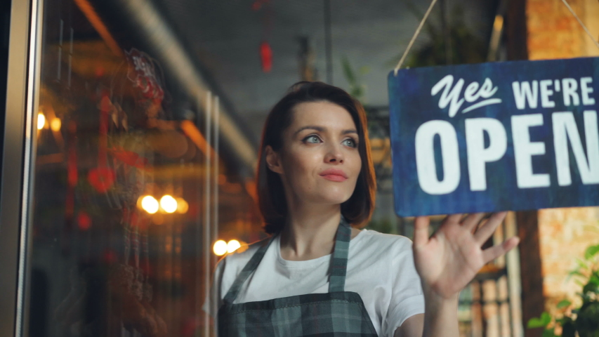 Business owner attractive woman in apron hanging we're open sign on front door smiling welcoming clients to new cafe. Business, people and youth concept.