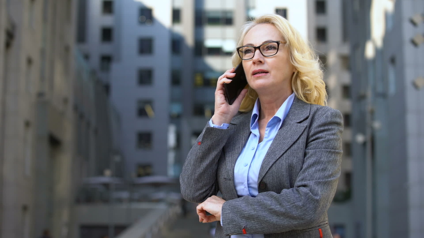 Aged female realtor showing yes gesture talking on phone, business deal approval | Shutterstock HD Video #1032111305