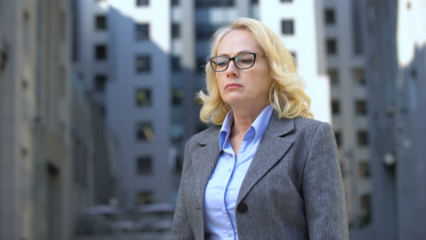 Pensive female director in eyeglasses standing outdoors, work stress, anxiety | Shutterstock HD Video #1032111455