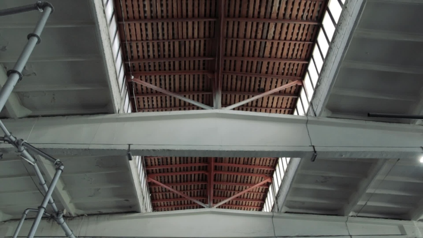 A slow-motion camera moves along a large gray high empty storage room in a factory with bright lighting on the ceiling | Shutterstock HD Video #1032130055