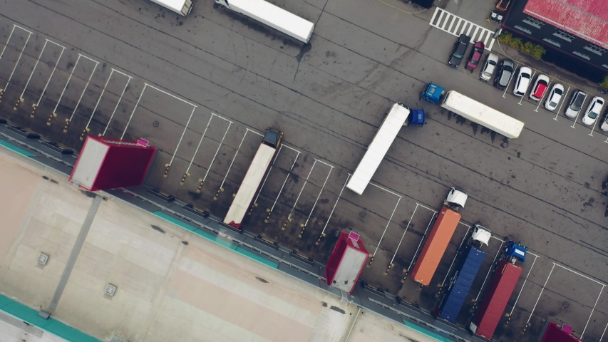 Aerial Shot of Industrial Warehouse Loading Dock where Many Truck with Semi Trailers Load Merchandise. #1032132335