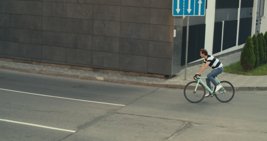 Cyclist guy riding fixed gear sport bike in sunny day on city. Hipster man in casual summer cloths and bicycle on street. 4K slow motion raw video footage 60 fps | Shutterstock HD Video #1032171605