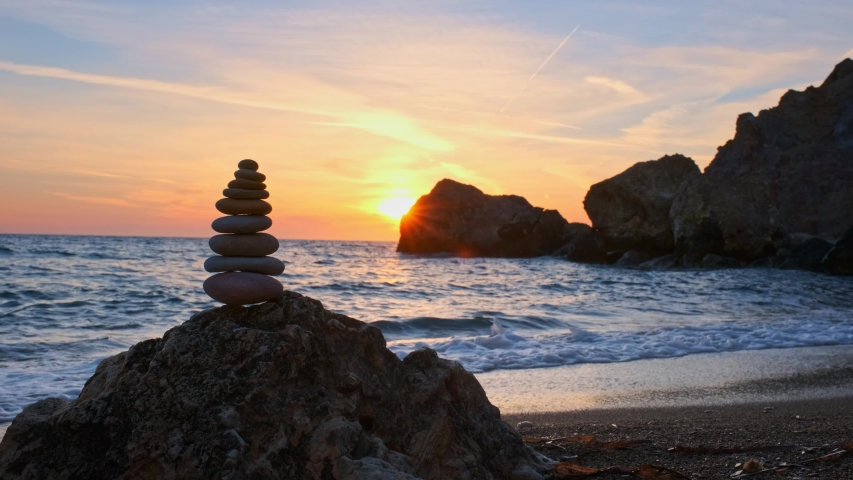 Concept of balance and harmony. Stack of stones pebbles cairn on the beach coast of the sea in the nature on sunset. Meditative art of stone stacking | Shutterstock HD Video #1032218375