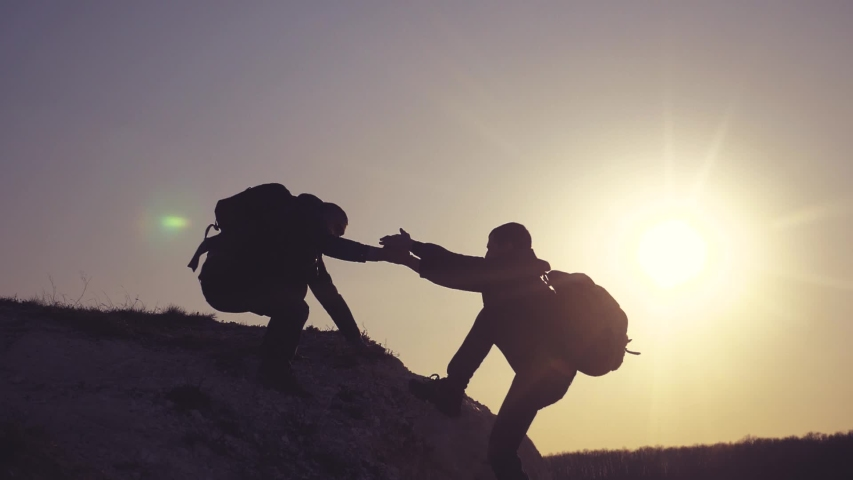 Teamwork help business travel silhouette concept. group of tourists lends a helping hand climb lifestyle the cliffs mountains. people climbers climb to the top overcoming hardships the path to victory | Shutterstock HD Video #1032243275
