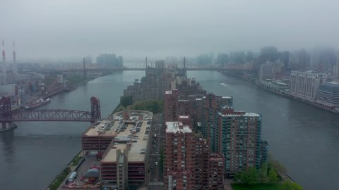 Drone flyover Roosevelt Island between Manhattan and Queens NYC on a very foggy day. View of Queensboro bridge and vistas of the city in broody fog. in 4K.