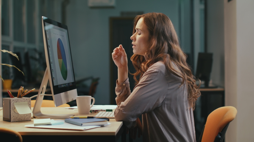 Upset business woman looking at financial report on computer in office at night. Nervous female professional finding mistake in charts at evening office. Shocked woman working overtime with documents.