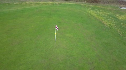 Panoramic drone shot of a red and white golf flag,ing in the wind, on a bright green golf field, on a sunny day