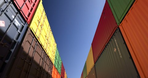 Rows of cargo shipping containers under clear sky. Industrial containers are excellent for cargo import export shipment. Camera endlessly moves thru cargo boxes of different transportation companies