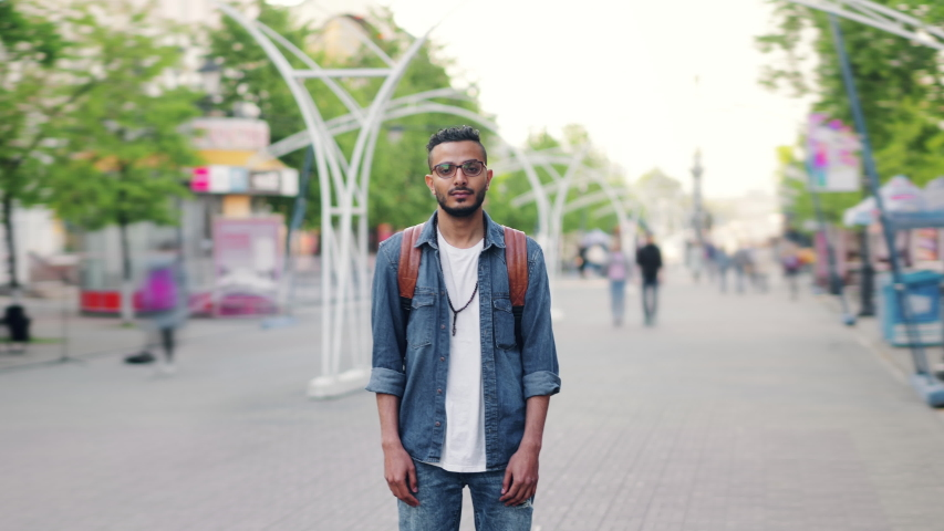 Zoom-out time lapse of attractive young man Arab standing in busy street with backpack looking at camera with serious face. Life, people and society concept.