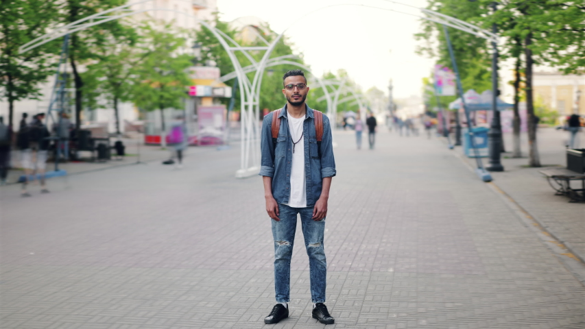Time lapse portrait of Arabian guy standing in the street with backpack alone among crowd of people and looking at camera. Youth, city and tourism concept.