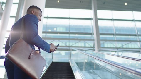 young african american businessman using smartphone on escalator texting checking email messages online successful male executive arriving at work in corporate office building 4k