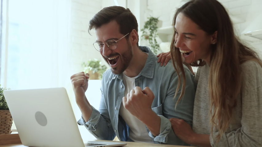 Lucky overjoyed happy young couple using looking at laptop computer excited by online bet bid win feel winners euphoric celebrating by internet lottery victory prize good news got new opportunity | Shutterstock HD Video #1032517145