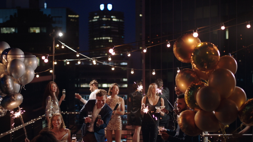 Friends celebrating new years eve party dancing throwing confetti enjoying glamorous celebration wearing stylish fashion at formal social gathering on rooftop at night 4k | Shutterstock HD Video #1032519995