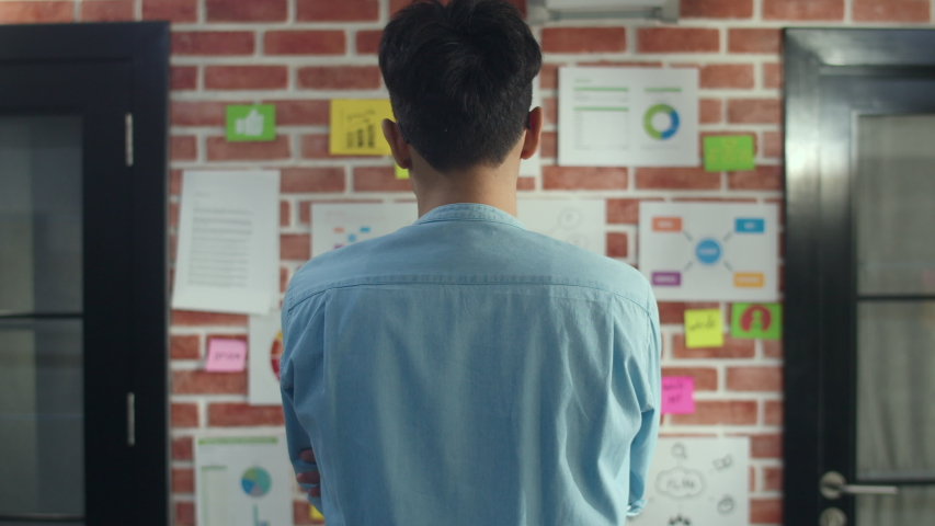 Asian creative man standing looking work plan on paper board. Young professional business male think and write information reminder on brick, business situation, startup in Loft office concept. | Shutterstock HD Video #1032523505