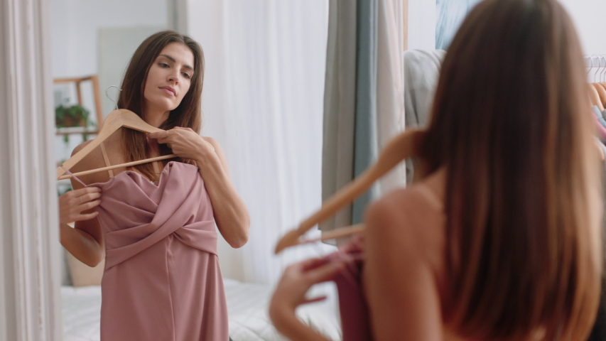 Beautiful young woman getting dressed looking in mirror choosing outfit fashion choice putting on clothes enjoying positive self image feeling confident at home 4k footage | Shutterstock HD Video #1032526745