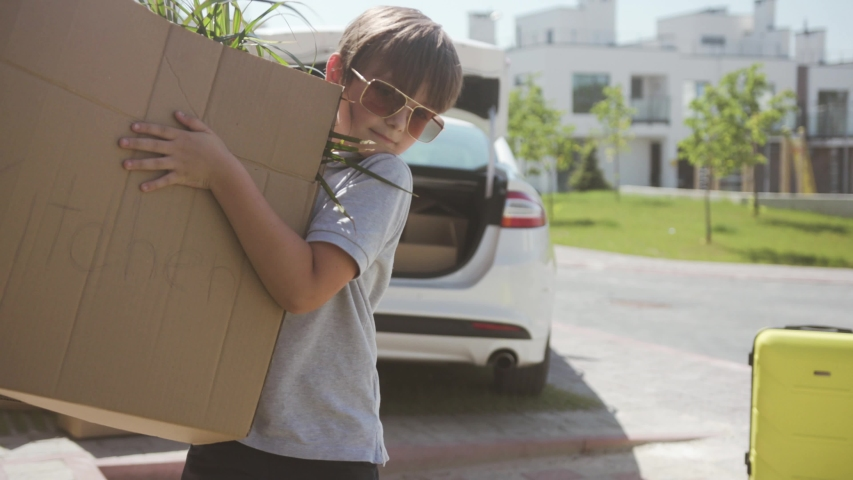 Excited young modern family moving to a new apartment in a beautiful neighbourhood. Portrait of a cute strong boy carrying big boxes to the house on sunny day.