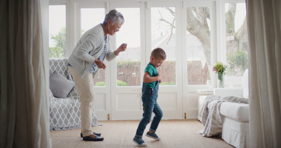 happy little boy dancing with grandmother funny granny having fun dance with grandson celebrating family weekend at home #1032772805