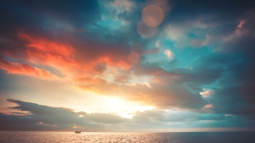 Romantic colorful sunset at the sea. Sun go down, blue and orange clouds flow in sky. Majestic summer landscape. Exploring beauty world, travel, holidays, recreation. Slow motion timelaps 4K footage