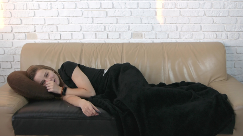 Beautiful young caucasian woman watching tv lying on a comfortable sofa smiling and laughing.  | Shutterstock HD Video #1032849185