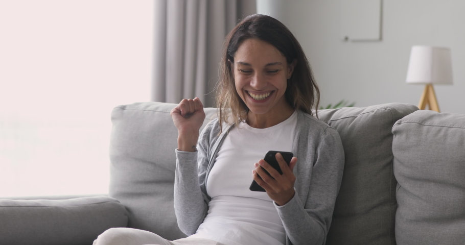Happy overjoyed girl holding phone celebrate good mobile news surprise bid win game app victory sit on sofa at home, excited young woman winner screaming yes rejoicing success looking at cellphone