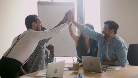 Happy successful multiethnic business team give high five sit at table, motivated diverse executives group engaged in teambuilding celebrate good teamwork result achieved corporate goals concept