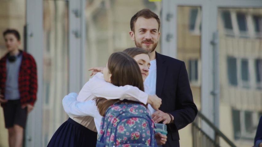 Happy smiling parents leading their cute daughter to school hugging together in the school courtyard. First day of studies. | Shutterstock HD Video #1032918215