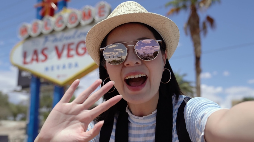Young asian college girl student study abroad in usa. female teenager talking on video phone call with family while standing by Las Vegas Welcome sign. woman presenting and inviting to come to camera | Shutterstock HD Video #1032932765