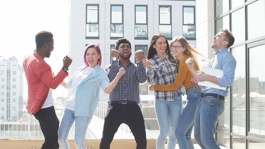 Group of multi ethnic young colleagues celebrates success on terrace of modern office. | Shutterstock HD Video #1033097975