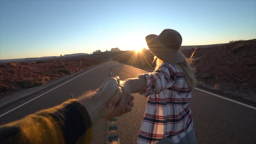 Follow me to concept; young woman leading boyfriend on empty highway in USA at sunset; Couple holding hands following each other near Monument Valley - slow motion    Shutterstock HD Video #1033112765