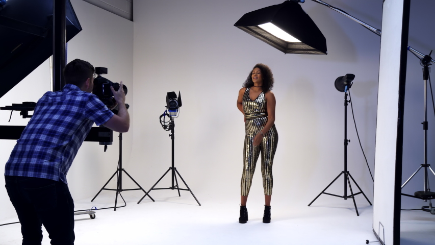 Male Photographer Working With Female Model On Fashion Shoot In Studio  | Shutterstock HD Video #1033121525