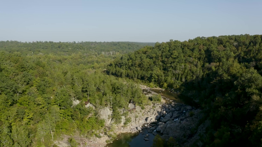 Aerial flight over forests, bluffs and a river - flying away from the river   Shutterstock HD Video #1033139075