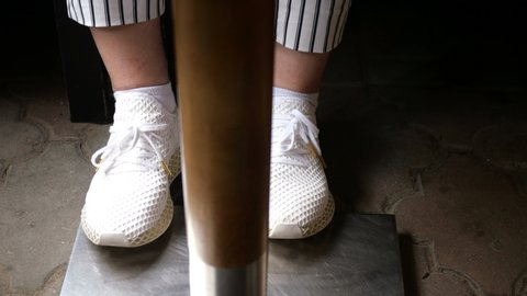 5295b83ec99 Legs of a woman in white sneakers and black-and-white striped pants stomp  under the table.
