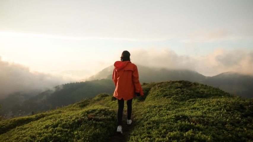 Camera follows hipster millennial young woman in orange jacket running up on top of mountain summit at sunset, jumps on top of rocks, raises arms into air, happy and drunk on life, youth and happiness | Shutterstock HD Video #1033184645