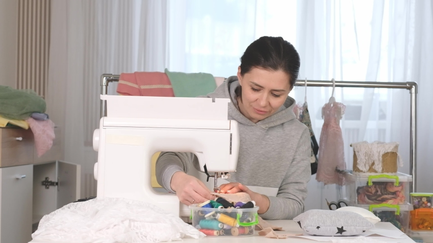 Beatiful tailor is practicing her hard job at nicely organised place | Shutterstock HD Video #1033207565