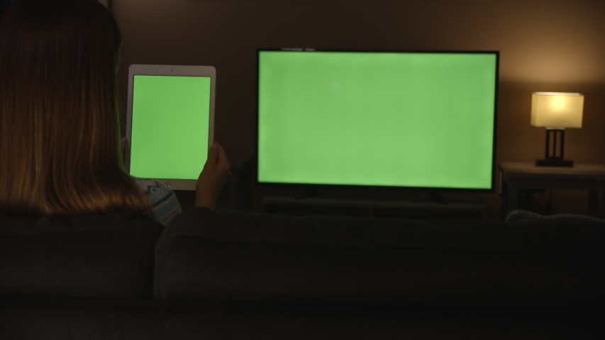 Woman watching green screen tablet and scrolling and tv in evening, 4k #1033241495