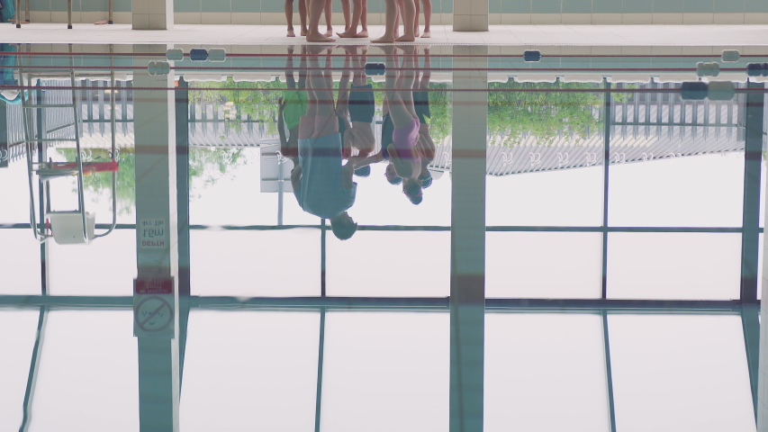 Male Coach Giving Children In Swimming Class Instructions As They Stand On Edge Of Indoor Pool | Shutterstock HD Video #1033265255