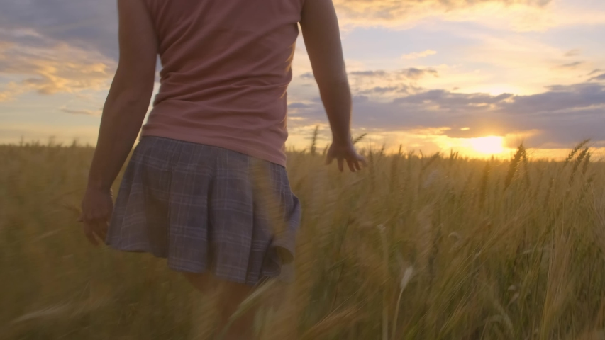 happy girl in short skirt runs skipping in wheat field at sunset. concept of freedom. #1033277735