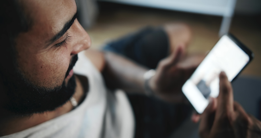 Young handsome bearded male sitting indoors and browsing social network on smartphone, modern communication | Shutterstock HD Video #1033278725