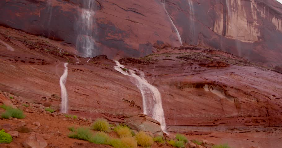 multiple waterfalls of rainwater gush down red rock canyon wall at Lake Powell/Glen Canyon National Recreation Area