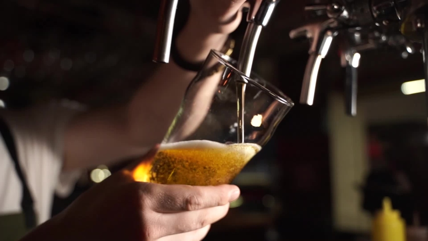 Bartender pouring beer into glass with bubbles close up | Shutterstock HD Video #1033584725