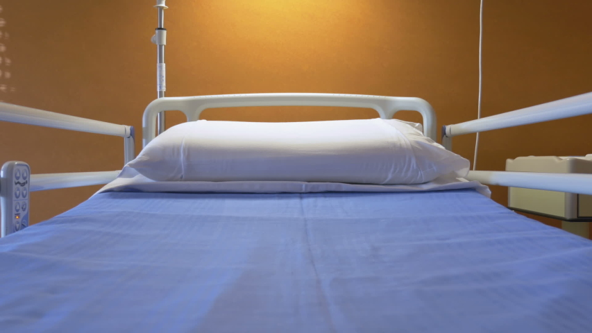 Medical bed with remote control hanging on the bed rail in a hospital. Modern healthcare technology and medical equipment. | Shutterstock HD Video #1033696115