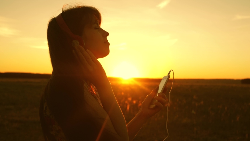 girl travels and listens to music and dances in rays of the sunset. a young girl in headphones and with a smartphone touches finger to the sensor of the tablet selects songs online. Slow motion. #1033744595
