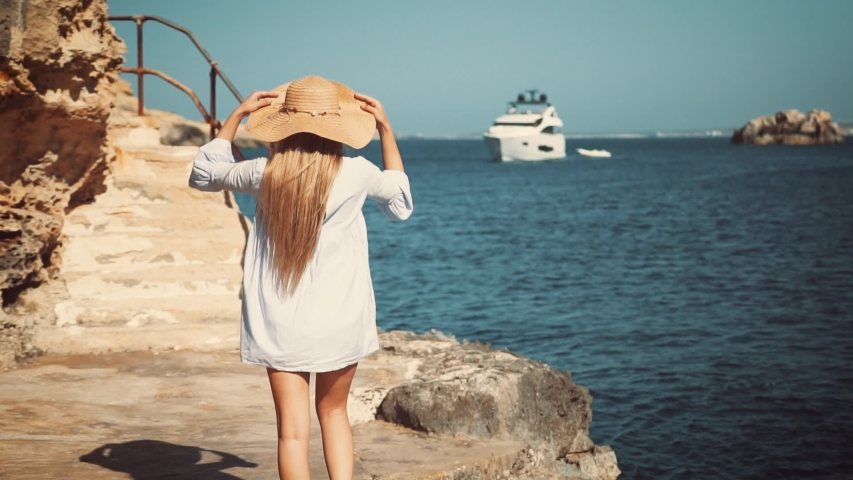 Sexy girl in a wheat hat and long shirt is walking along the rocky coast towards luxury yacht in the background.