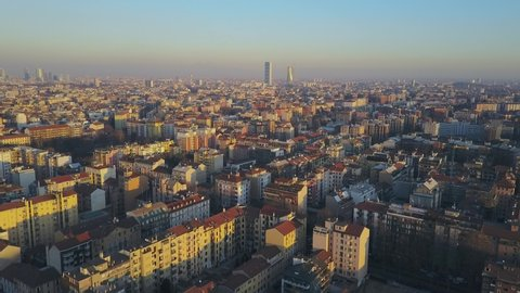 Milan city skyline aerial view at dawn flies backwards. The theatrical performance shot from the Milan cityscape in the fall. Aerial footage. A short flight that shows the city of Milan skyscrapers