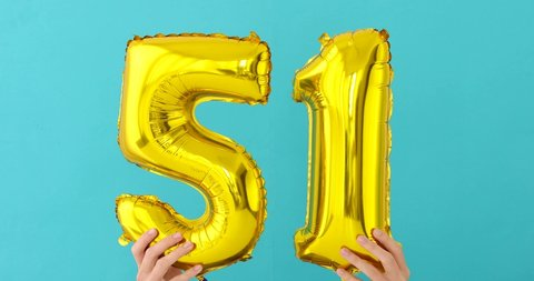 Gold foil number 51 fifty one celebration balloon on a blue background